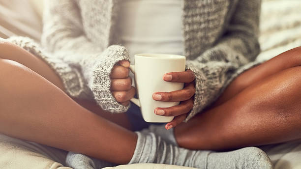 Weekend bliss Shot of an unidentifiable young woman enjoying a cup of coffee while sitting on her couch at home cross legged stock pictures, royalty-free photos & images