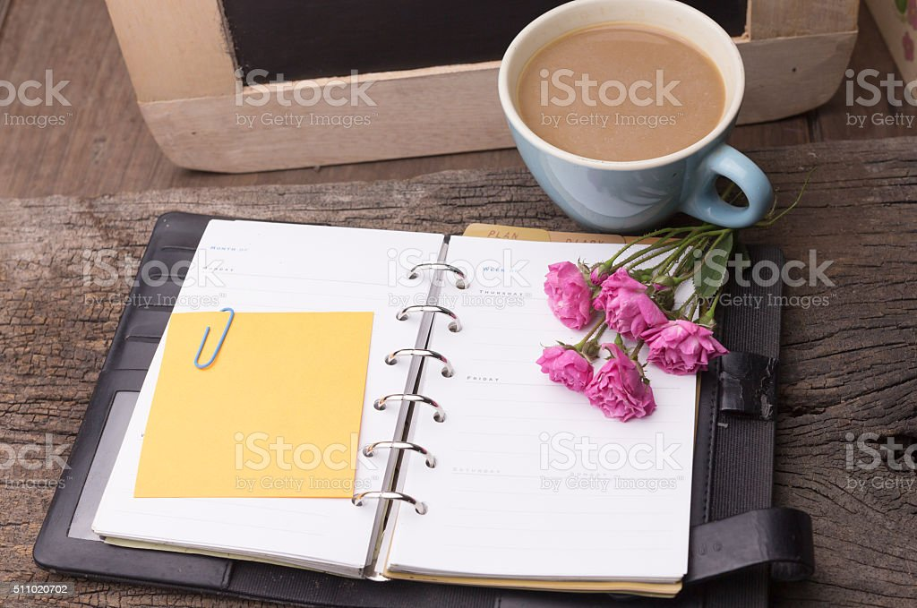 Weekend concept. Pink rose, mug with coffee, diary for note stock photo