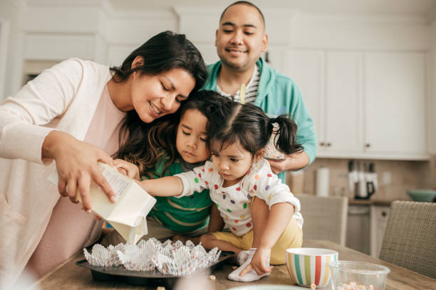 Weekend family time Family of four baking together spanish and portuguese ethnicity stock pictures, royalty-free photos & images