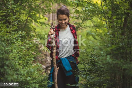 A young girl is spending a sunny day in nature, hiking. She is walking with a big stick in her hand to help her get through the branches.