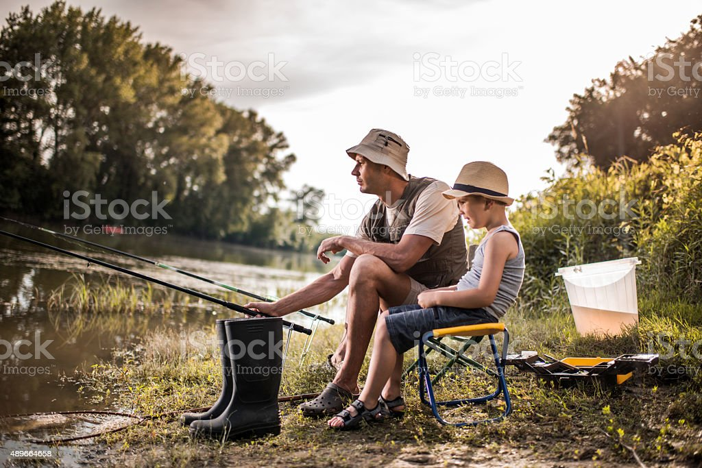 Weekend river fishing of a father and son. stock photo