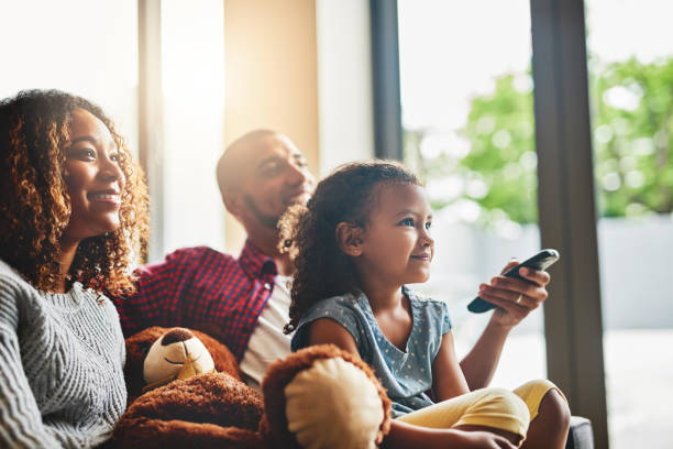weekends are about doing what everybody loves - family watching tv stock photos and pictures