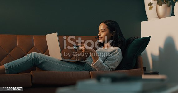 Shot of an attractive young woman using her credit card and laptop to shop online while relaxing at home