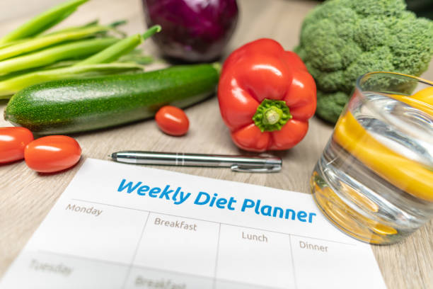 Weekly Diet Planner with lots of healthy vegetables stock photo