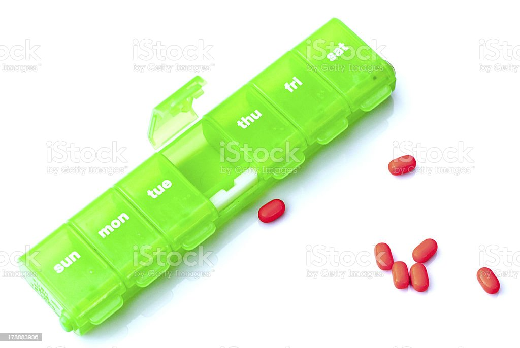 Weekly Pill Container with Red Pills on White Background stock photo