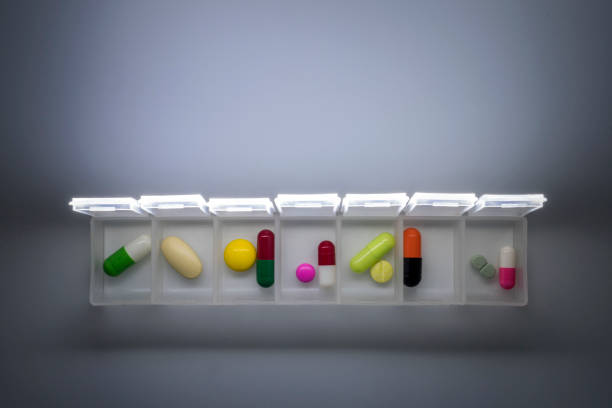 weekly pillbox with medication, conceptual image, horizontal composition - доза стоковые фото и изображения