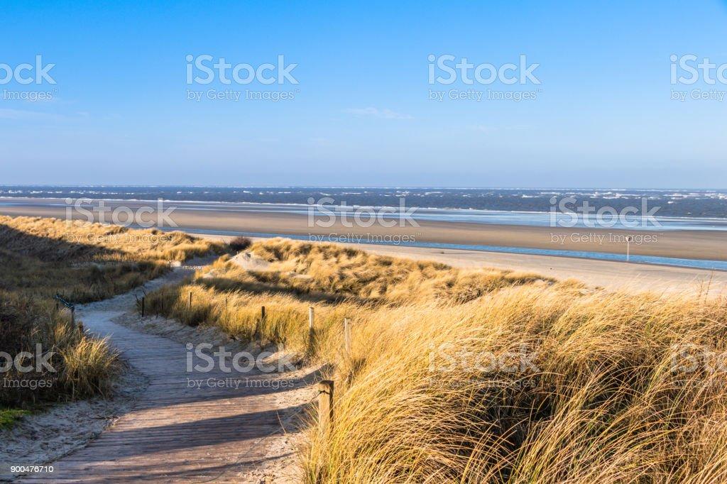 Weg durch die Dünenlandschaft zum breiten Strand auf der Nordseeinsel Spiekeroog im Winter stock photo