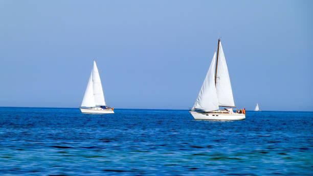 weiße segelboote oder yachten auf einem see oder dem meer bei sonnigem wetter und blauem wasser - wasser stock pictures, royalty-free photos & images