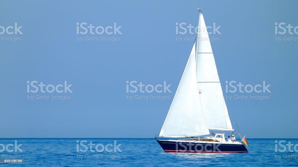 weißes Segelboot oder Yacht auf einem See oder dem Meer bei sonnigem Wetter und blauem Wasser stock photo