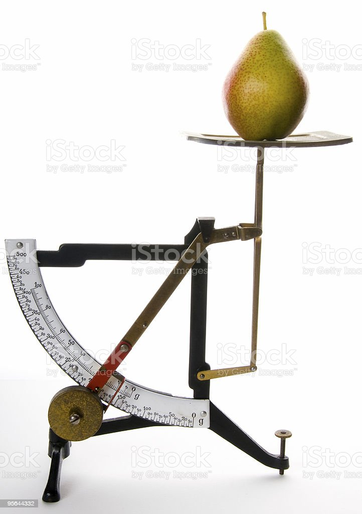 Weighing a Pear on an Old Kitchen Scale royalty-free stock photo