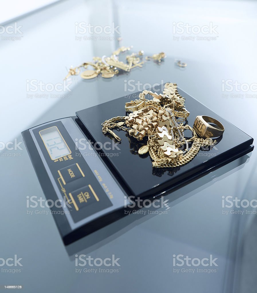 Weighing a pile of gold on the scales stock photo