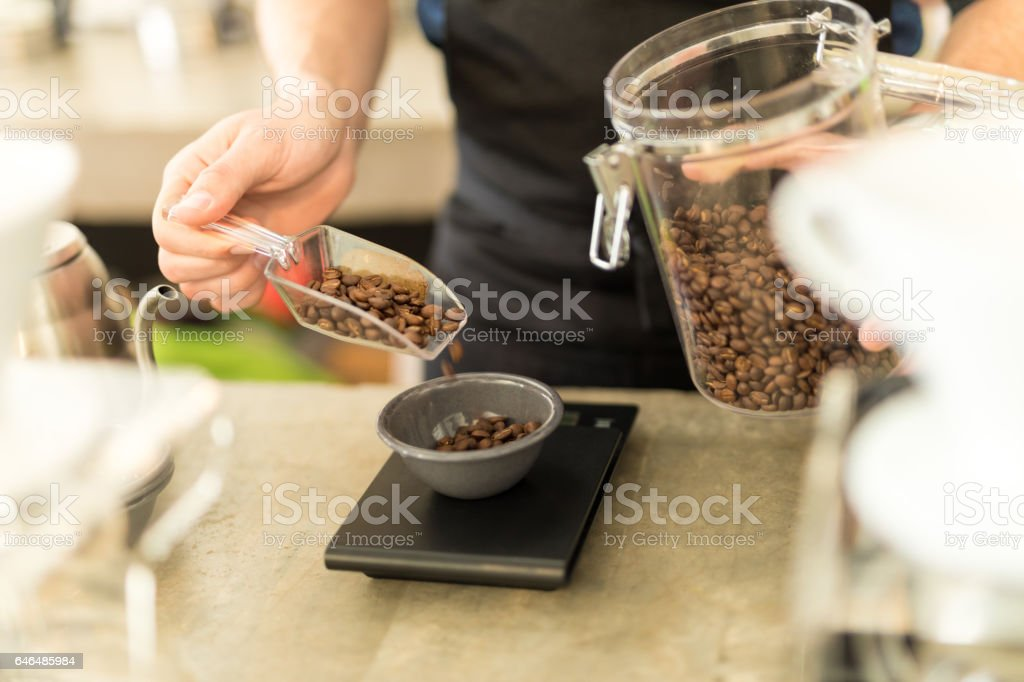 Weighing coffee grains on a scale stock photo