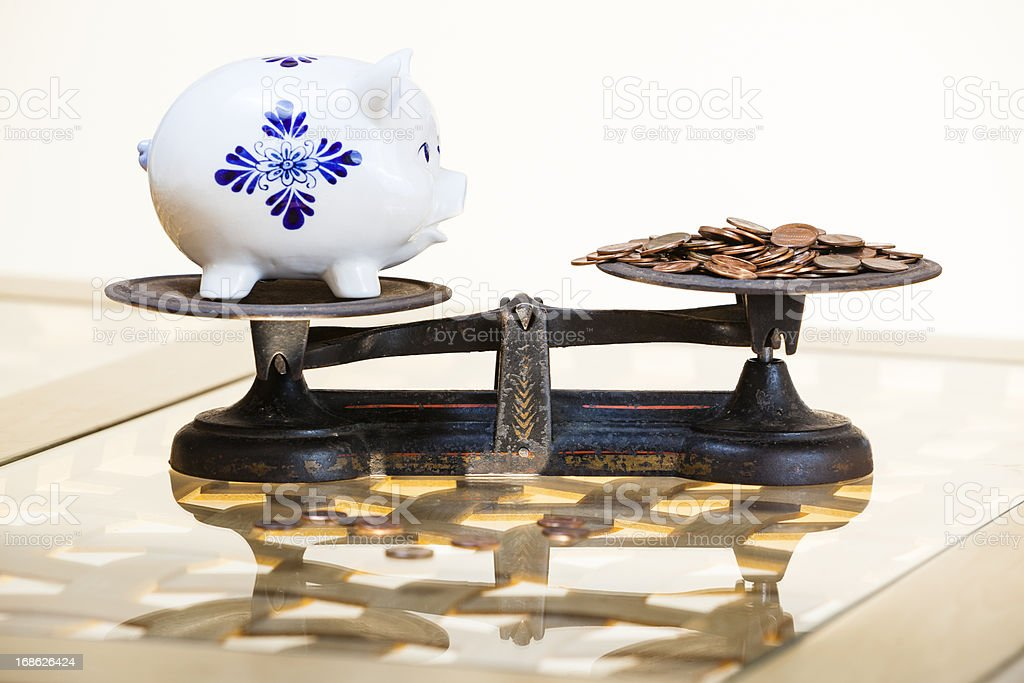 weighing of money for piggibank stock photo