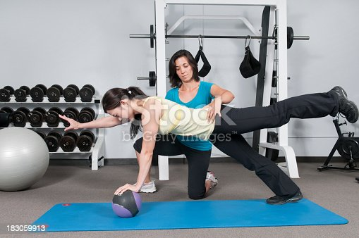 Woman working with her personal trainer using a weight ball for balance and strength training.