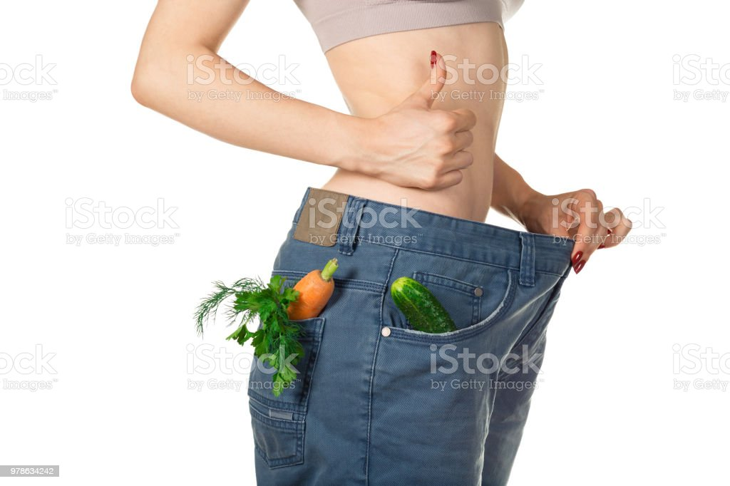 Weight loss and healthy eating or dieting concept. Slim girl in oversized jeans with raw vegetables in the pockets is holding her thumb up. Side view. Close shot stock photo