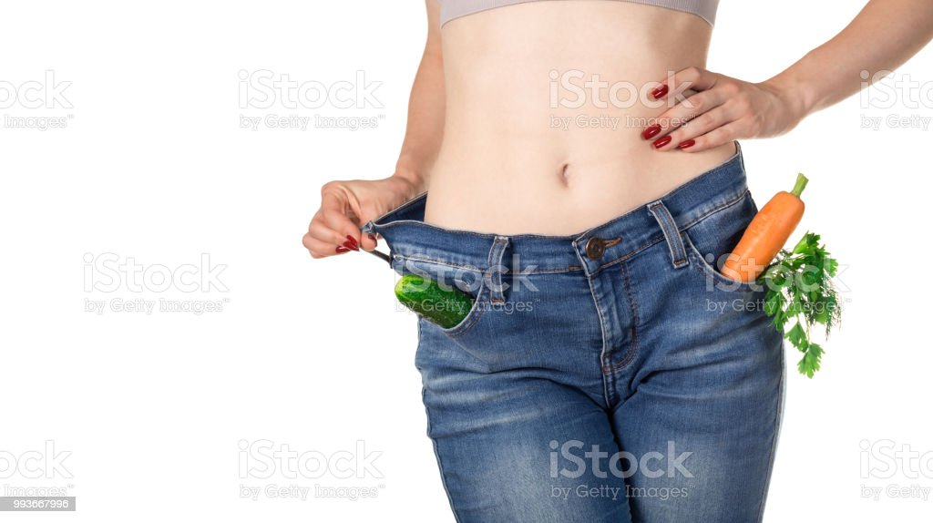 Weight loss and healthy eating or dieting concept. Slim girl in oversized jeans with raw vegetables in the pockets. Front view. Close shot stock photo