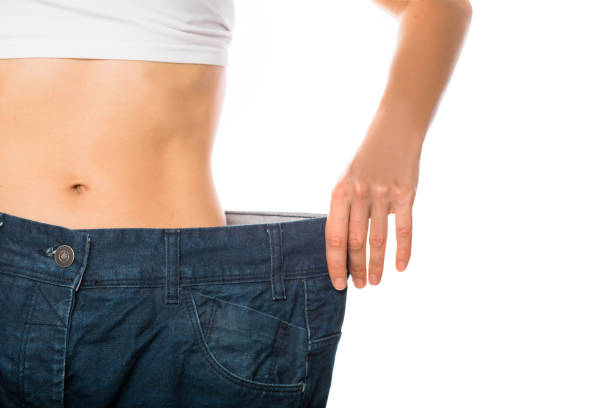Weight loss and slimming Slim stomach of young woman, thin body with perfect waist, showing her jeans after successful diet or sport training on isolated background. Weight loss and slimming dieting stock pictures, royalty-free photos & images