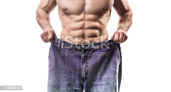 Weight loss, close up of muscular built man wearing too large jeans isolated on white background