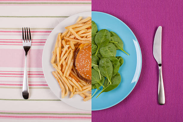 weight loss concept stock image of low fat healthy spinach leaves against unhealthy greasy burger with french fries. diet concept unhealthy eating stock pictures, royalty-free photos & images