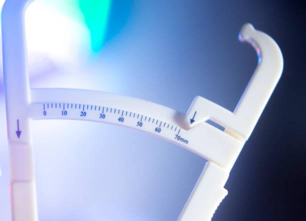 Peso perda dieta gorda compassos de calibre para medir os níveis de gordura corporal - foto de acervo