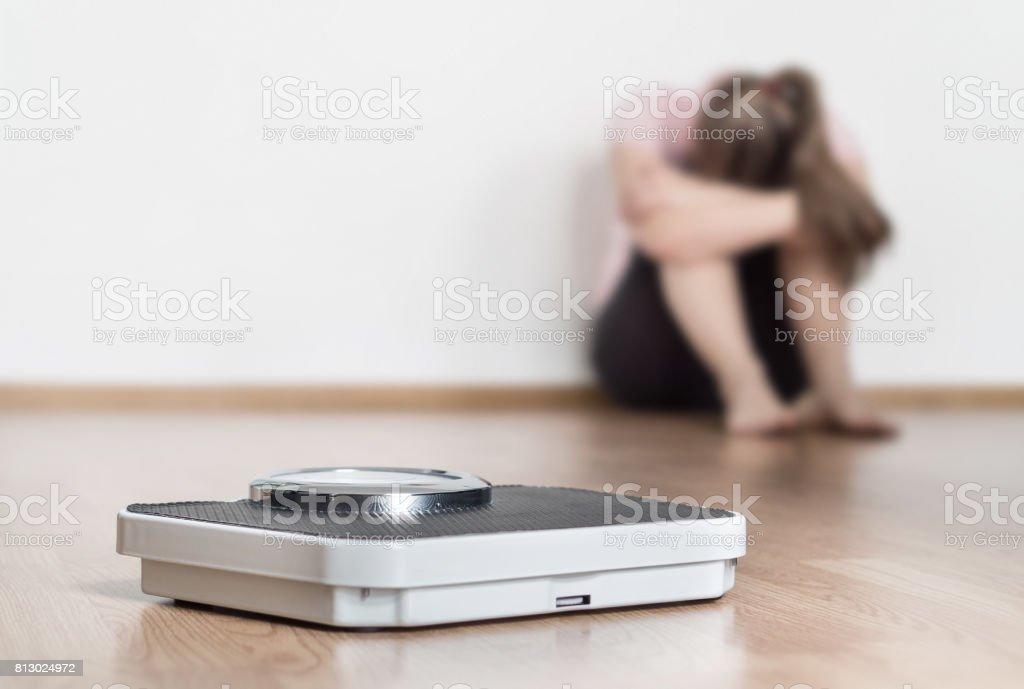 Concepto de error de pérdida de peso. Escala y deprimida, frustrada y triste mujer sentada en el piso sosteniendo la cabeza y los brazos en las rodillas. - foto de stock