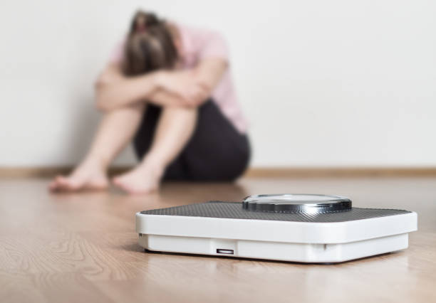 Weight loss fail concept. Scale and depressed, frustrated and sad woman sitting on floor holding head and arms on knees. stock photo