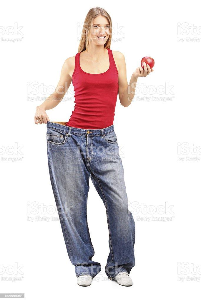 체중 손실 female 쥠 자신의 jeans 및 사과나무 royalty-free 스톡 사진