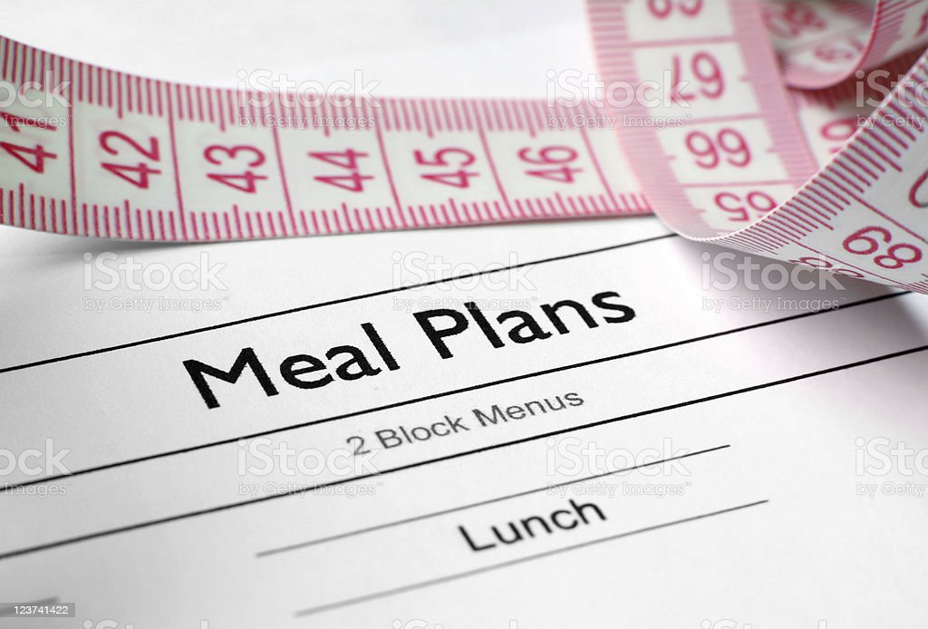A weight loss meal plan sheet alongside a tape measure stock photo