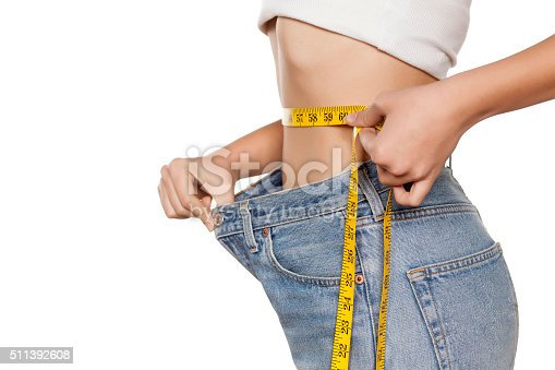 woman posing with a measuring tape and a big size pants