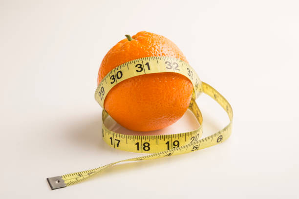Weight loss solution concept. Orange with measure tape. Good source of Vitamin C stock photo