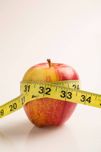 Weight loss solution concept. Red apple with measure tape stock photo