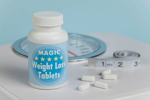 Weight Loss Tablets, Scale and Tape Measure stock photo
