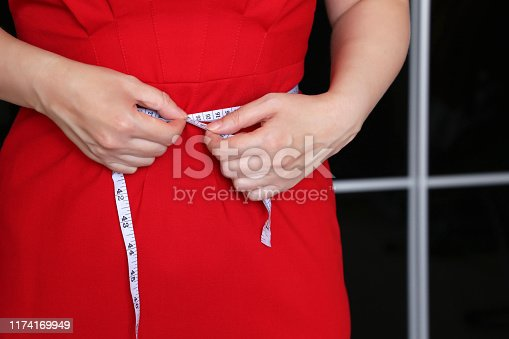 1184112328 istock photo Weight loss, woman in red dress with measuring tape around the waist 1174169949