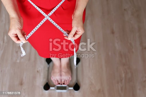 1184112328 istock photo Weight loss, woman in red dress with measuring tape around the waist stands on a scale 1178831378