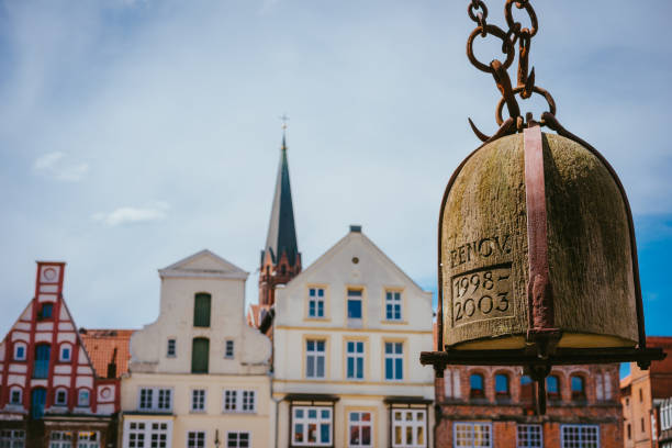 Weight of old Crane hanging in front of facade of historical buildings in Harbor Lueneburg, Lower Saxony,Germany Weight of old Crane hanging in front of facade of historical buildings in Harbor Lueneburg, Lower Saxony,Germany. lüneburg stock pictures, royalty-free photos & images