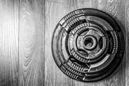 istock Weight plate. Bodybuilding equipment. Gym floor. Black and white. Barbell. 700891254