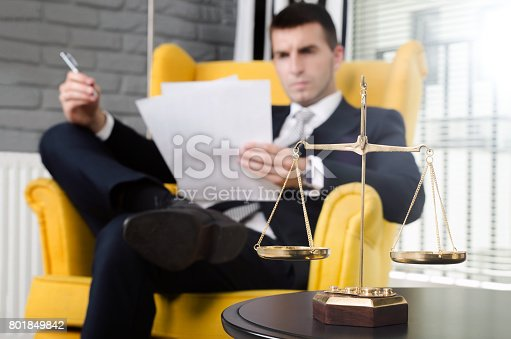istock Weight scale of justice, lawyer in background 801849842