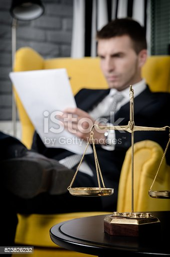 istock Weight scale of justice, lawyer in background 823826232