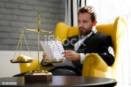 istock Weight scale of justice, lawyer in background 823826506