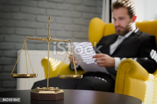 istock Weight scale of justice, lawyer in background 842451642
