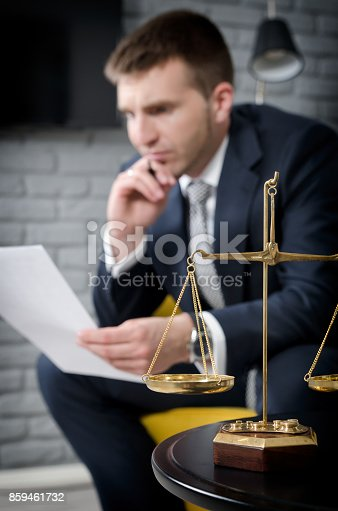 istock Weight scale of justice, lawyer in background 859461732