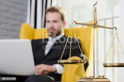 istock Weight scale of justice, lawyer in background 862302536
