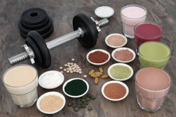 Weight Training Equipment and Supplements Weight training equipment for body builders with dumbbell weights, dietary food supplements and vitamins with health drink selection. amino acid stock pictures, royalty-free photos & images