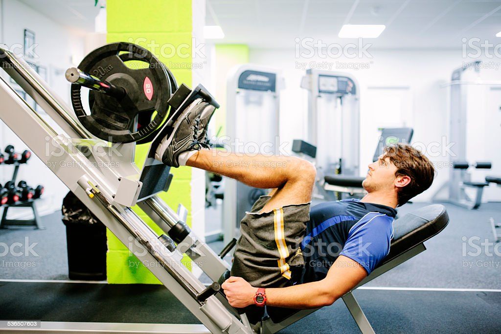 Weight training in the gym, using a leg press stock photo