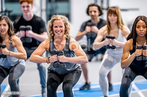 A multi-ethnic group of adults are indoors in a fitness center. They are lifting dumbbells and squatting.