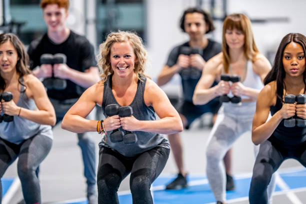 Weighted Squats A multi-ethnic group of adults are indoors in a fitness center. They are lifting dumbbells and squatting. exercise class stock pictures, royalty-free photos & images