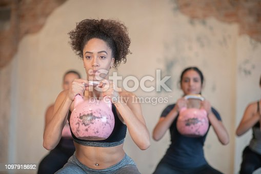A group of women are at a fitness center. They are doing squats with kettle weights.