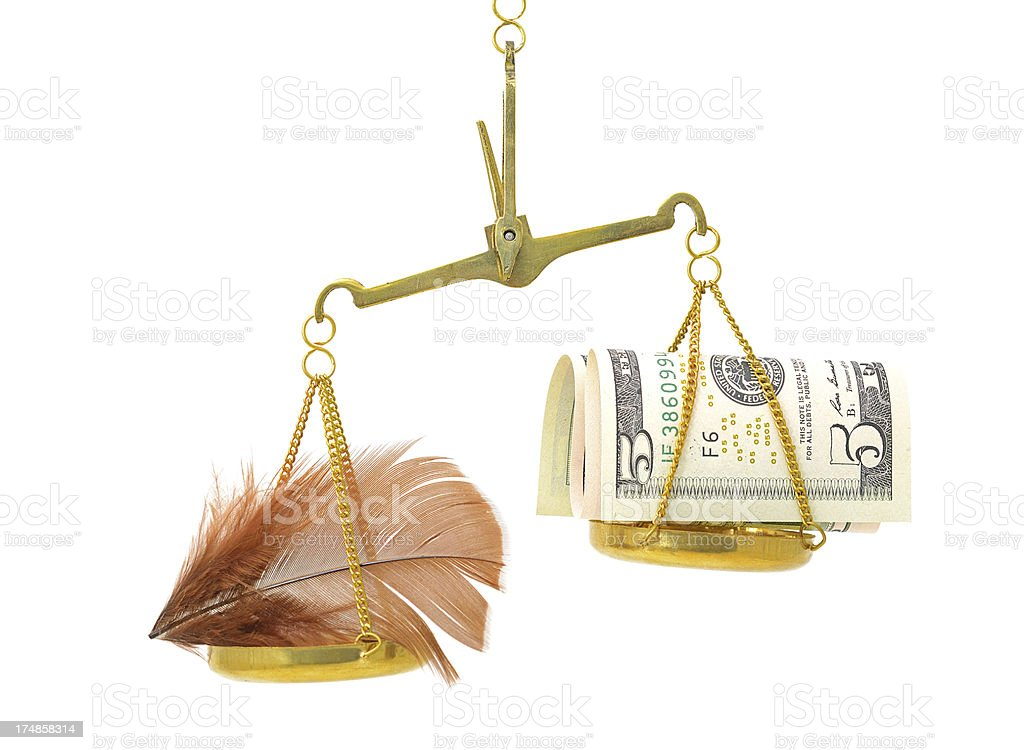 Weighting  money against a feather on scale royalty-free stock photo