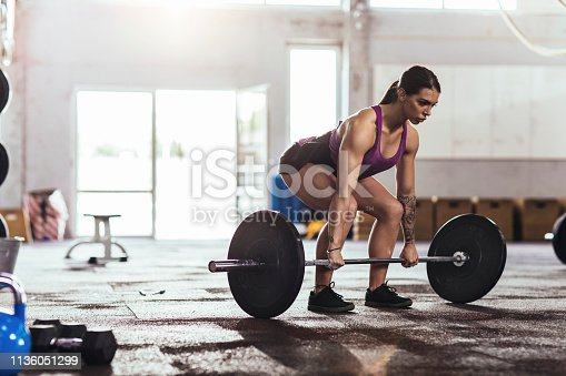 Pretty athletic woman weightlifting in the gym