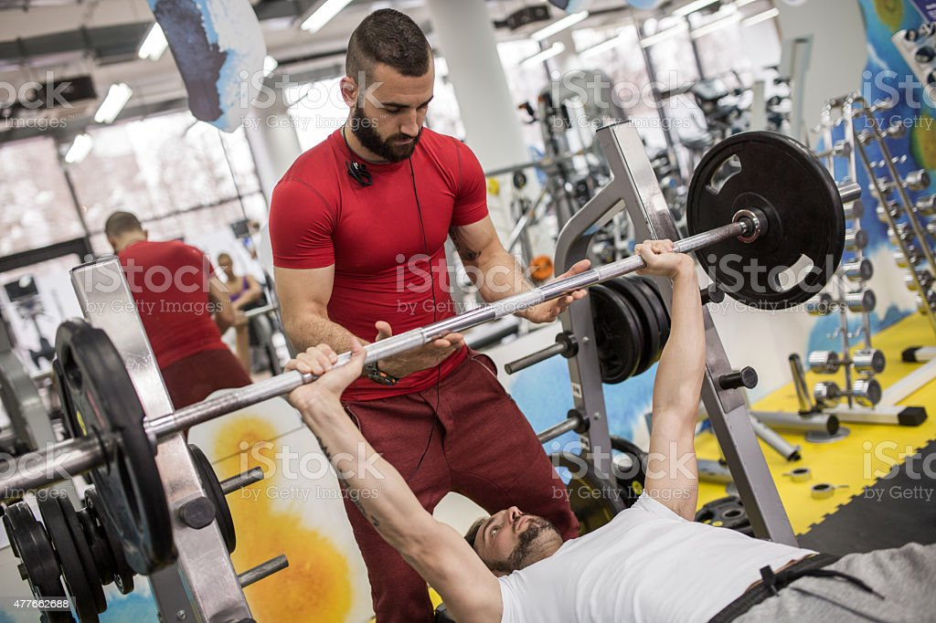 Weightlifting training with fitness instructor in a gym. stock photo